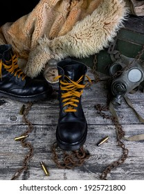 Leather boots with rusted chains and bullet shells with military gas mask and fur coat in background resting on wooden table