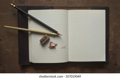 a leather bound journal lies open on a vintage desk. Pencils, shavings and a pencil sharpener rest on an open, blank page.