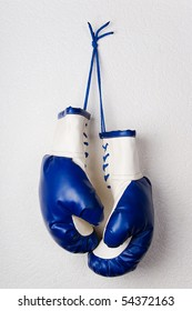 Leather boxing gloves hanging on wall.White&blue boxer gloves pair.Combative sports equipment,protect from injury.Sport accessories for professional sport.Pro boxing glove pair hanging on white wall