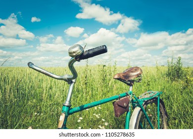 Leather brown bicycle saddle. Summer day for trip. View of wheat field. Outdoor. Closeup.
