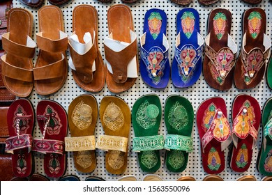 leather brown, colorful with a floral motif sandals and flip flops hanging on one of the stalls, souvenir shop on the streets of the Old City of Jerusalem