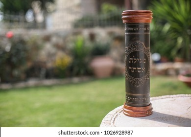 "Leather case with the inscription ""Scroll of Esther"", encasing the Jewish book of Esther, with a garden backround. Jews read the book of Esther, as part of the traditions of the holiday of Purim"