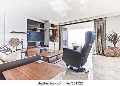 Leather chair close to television, living room with luxury furniture, walls are white, flower vase near window