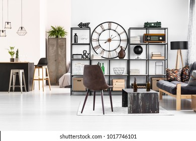 Leather chair standing next to an industrial table with beer bottles on it in manly flat interior with open living room