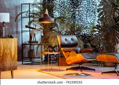 Leather chair and stool on pink carpet in vintage room with lamp above copper table