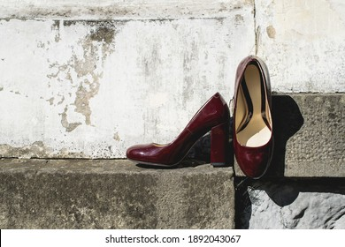 Leather cherry women's shoes on a stone wall. fashion concept, women's shoes, accessories. burgundy women's lacquered leather shoes