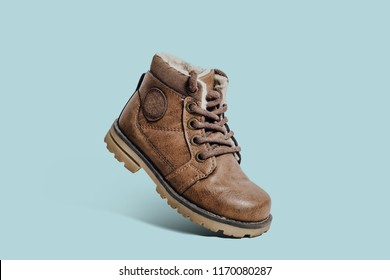 Leather, children's shoe on a pastel, blue background. The concept of upcoming cold, selling shoes. Warm, comfortable shoe for children with fur at an angle and inclination.