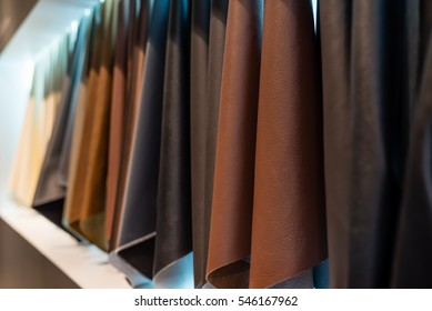 leather and cloth sample hanging on a white wall background (soft focus)