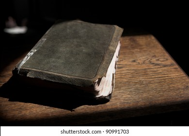 Leather covered old bible lying on a wooden table in a beam of sunlight Shallow Depth of field â?? Focus on Text â??Holy Bibleâ?�