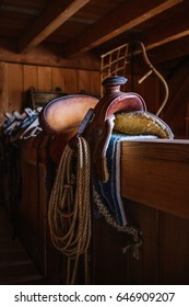 Leather cowboy horse saddle and lasso in a barn