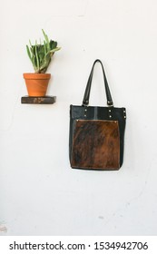 Leather and cowhide tote bag hanging on wall next to cactus, styled, copy space