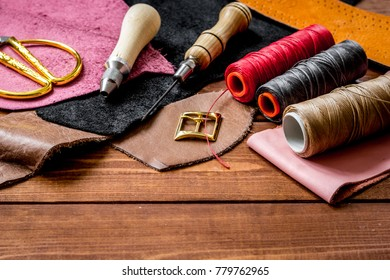 leather craft instruments on wooden background close up