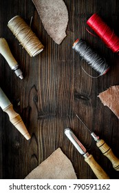 Leather craft. Knife, awl and other tools on dark wooden backgro