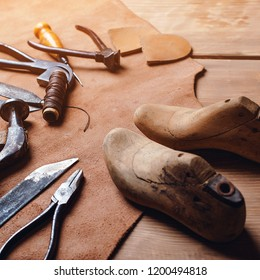 Leather craft tools on wooden background. Workplace for shoemaker. Piece of leather. Cobbler workplace with tools, leather and shoes last. Small shoemaker workplace with tools