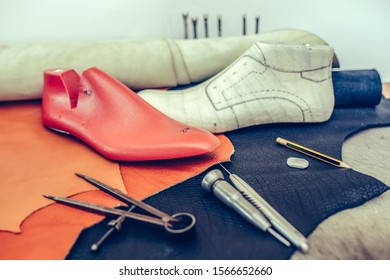 Leather craft tools on wooden background. Workplace for shoemaker. Piece of leather. Cobbler workplace with tools. Shoemaker workplace with tools. Selective focus and small depth of field.