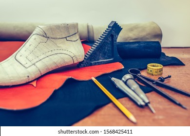 Leather craft tools on wooden background. Workplace for shoemaker. Piece of leather. Cobbler workplace with tools, leather and shoes last. Small shoemaker workplace with tools. Selective focus.