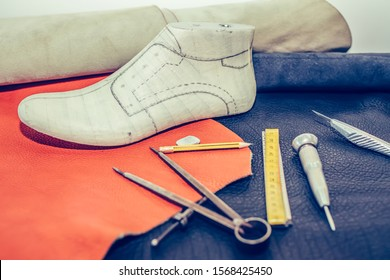 Leather craft tools on wooden background. Workplace for shoemaker. Cobbler workplace with tools, leather and shoes last. Shoemaker workplace with tools. Selective focus and small depth of field.