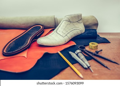 Leather craft tools on wooden background. Workplace for shoemaker. Piece of leather. Cobbler workplace with tools, leather and shoes last. Small shoemaker workplace with tools. Selective focus