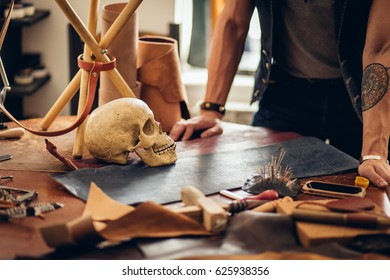 Leather craft tools and skull on a wooden background. Leather craftmans work desk . Piece of hide and working handmade tools on a work table.