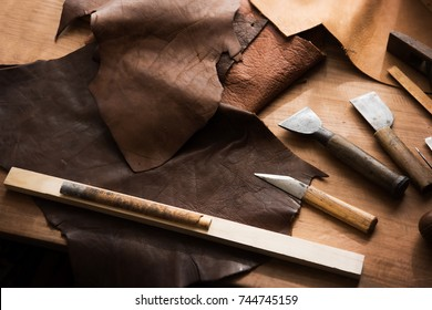 Leather craft or leather working. Large beautifully colored or tanned leather on leather craftman's work desk .