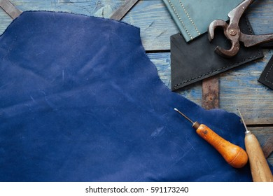 Leather craft and leather working. Piece of hide and working tools on a work textured blue table.