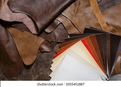 Leather craft or leather working. Pieces of leather and colored leather samples in the craftman's workshop. Top view.