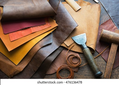 Leather craft or leather working. Selected pieces of beautifully colored or tanned leather on leather craftman's work desk . Piece of hide and working tools on a work table. - Shutterstock ID 476136478