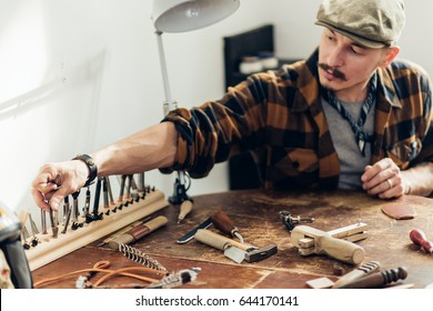 leather Crafter man dressed in plaid shirt takes tools