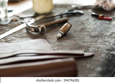 Leather crafting tools on working desk with a low depth of field