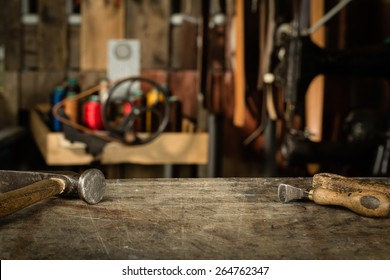 Leather crafting tools on working desk with the scratches. Blurred background of leather workshop. Copy space.