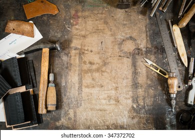 Leather crafting tools on working desk with the scratches. Grunge table. View from above. Copy space.