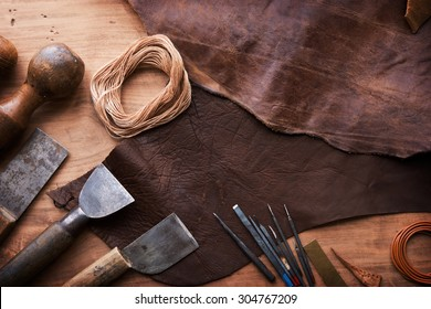 Leather craftmans work desk . Piece of hide and working tools on a work table.