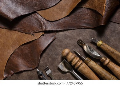 Leather craftman's work desk. Pieces of leather and working tools on a work table. Top view.