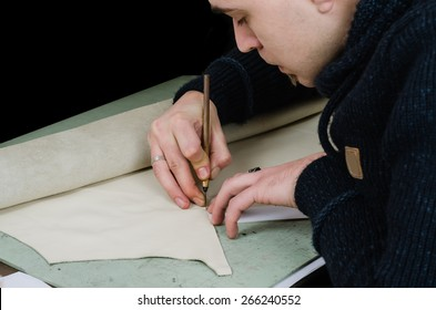 leather craftsman / shoemaker making a new lining for a wallet. Isolated on black background. Retro, nostalgic look