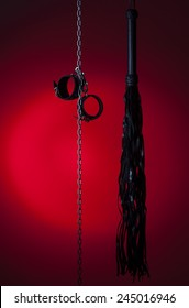 leather cuffs and a whip on a chain