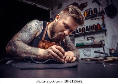 Lederschneider erstellt ein neues Lederprodukt in der Bannerwerkstatt