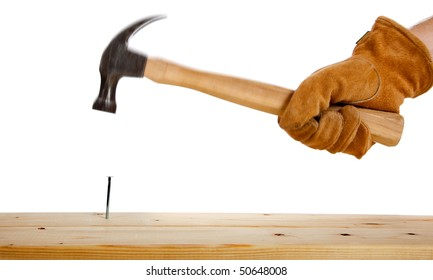 A leather gloved hammering a nail in a two by four on a white background