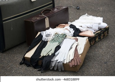 leather gloves with a suitcase standing on the pavement at a flea market in London