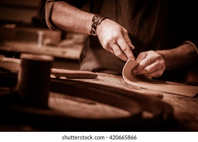 Leather goods craftsman at work in his workshop, France