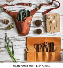 Leather holster, canvas, florist tools and flowers on a wooden background   - Shutterstock ID 1734732155