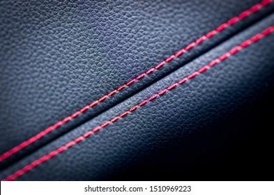 Lederinnenausstattung des modernen Luxusautos. Perforiertes Leder bequeme Sitze mit Heften. Moderne Details im Autoinnern. Autodetails. Auto drinnen. Lederstrukturhintergrund.