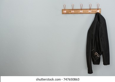 Leather jacket hanging on hook against wall