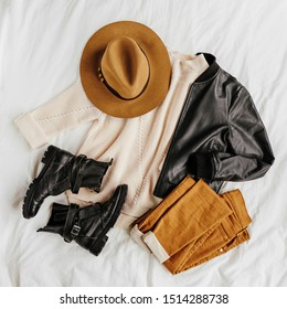 Leather jacket and white warm sweater with brown trousers and hat on white sheet. Women's stylish autumn or winter outfit. Trendy clothes collage. Flat lay, top view.
