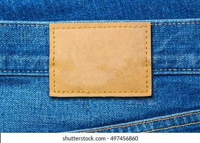 Leather label on denim blue jeans, fashion background, close up