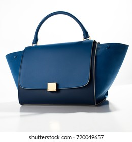 Leather luxury blue bag with gold accessories on a white background