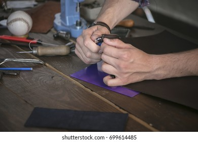 Leather maker cut leather with utility knife on wooden working table