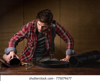 Leather master working holding a hole punch and a piece of leather. On brown wooden table scattered with tools and accessories.