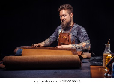 Ledermeister, der mit Lederarbeiten in einer Werkstatt arbeitet