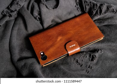 Leather phone case craftsmanship work on cloth background