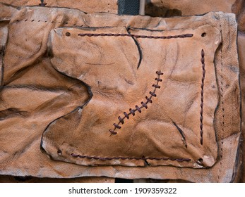 Leather pouch made of fresh zombie skin with scars stitched with dark brown thread top view